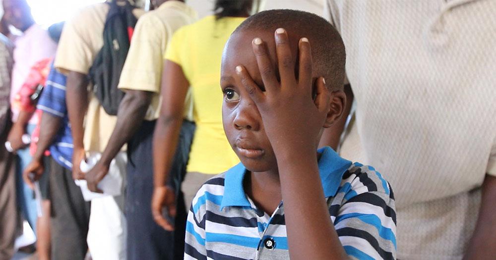 child holding hand over eye